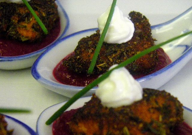 A blackened salmon bite served on an Asian spoon with a beet puree
